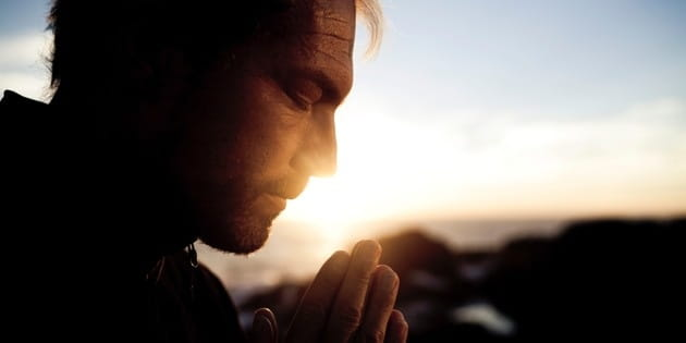 Man Praying at Sunrise Header