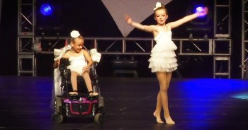 Older Sister Dances With Younger Sister In Wheelchair