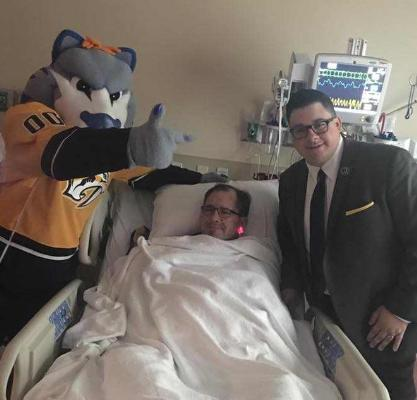 Tracy smiles with Gnash and Jared at his bedside